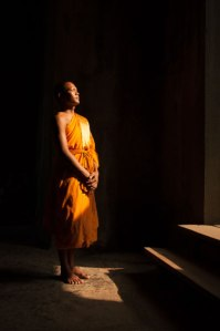 A monk inside an Angkor Wat gate.