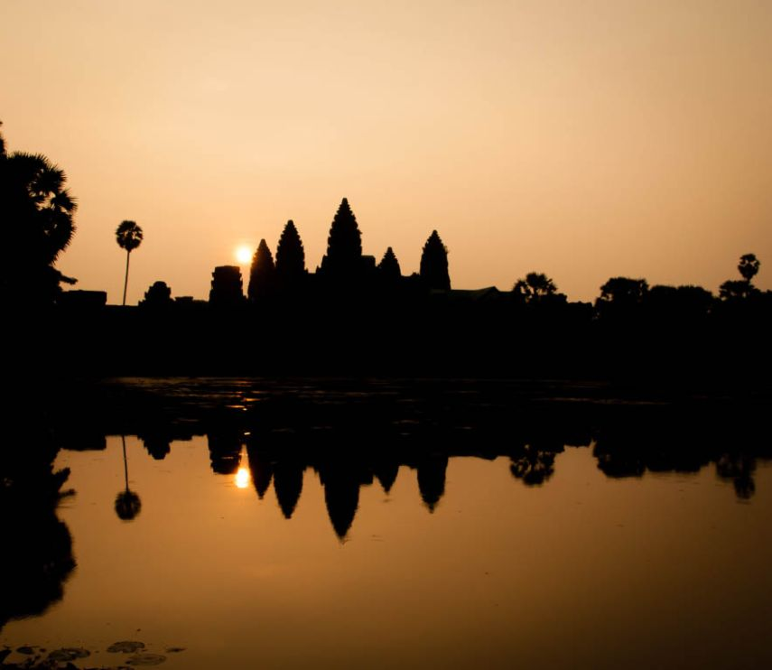 The sun rises behind Angkor Wat