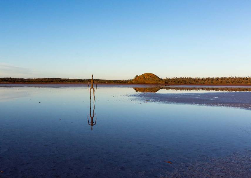 An Antony Gormley sculpture is reflected in water at Lake Ballard in Western Australia. Picture: CHRIS MANNOLINI