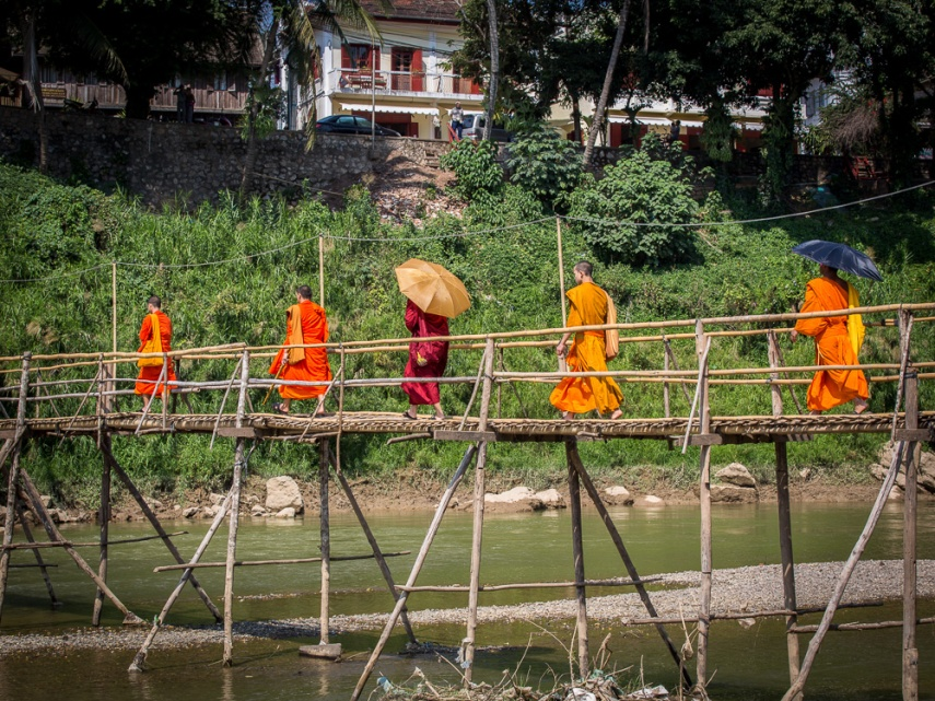 Monks cross the bamboo bridge over the Nam Khan in Luang Prabang, Laos. Picture: Chris Mannolini