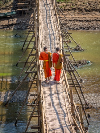 Two monks cross the bamboo bridge across the Nam Khan in Luang Prabang, Laos. Picture: Chris Mannolini