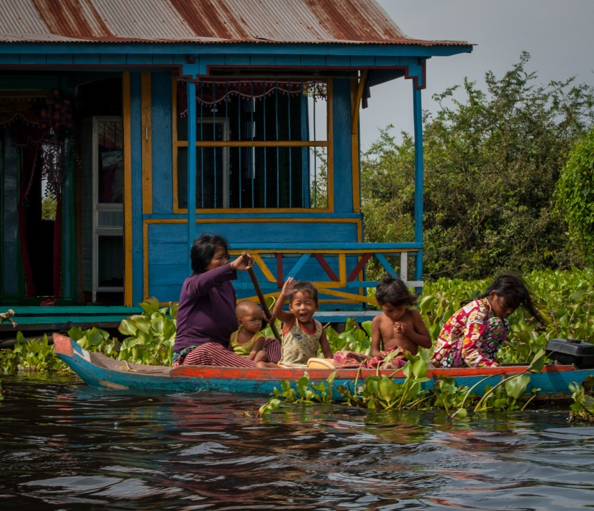 A young girl waves hello as the slow boat to Battambang passes her village in Cambodia's northwest.