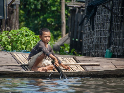 A boy on a boat at a village along the Sangkae river in northwest Cambodia. Picture: Chris Mannolini